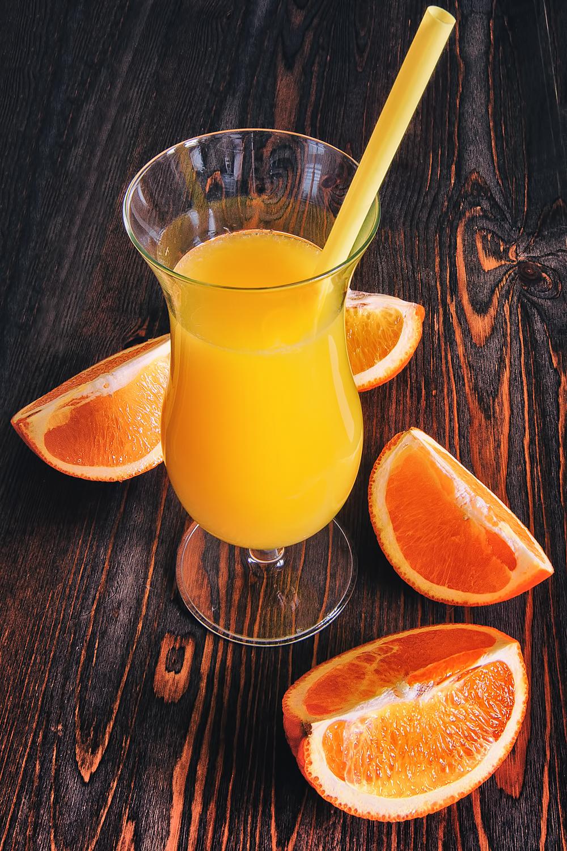 Stock image of orange juice and slices.